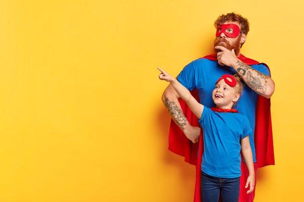 un papa et sa fille avec un déguisement de super héros