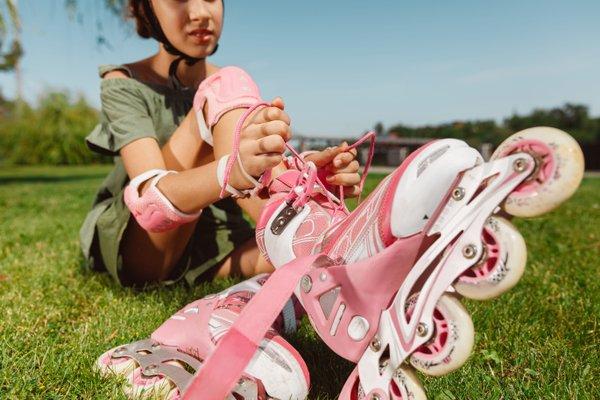 jeune fille qui chaussent ses rollers rose assisent sur le gazon