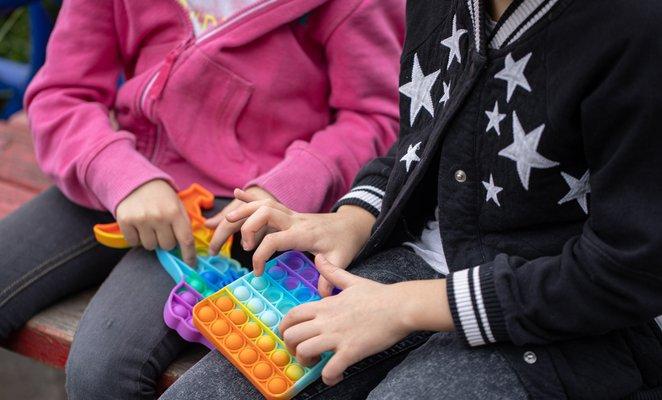 petites filles-jouant-nouveau-fidget-toy-populaire-avec enfants-aide-à-se-concentrer