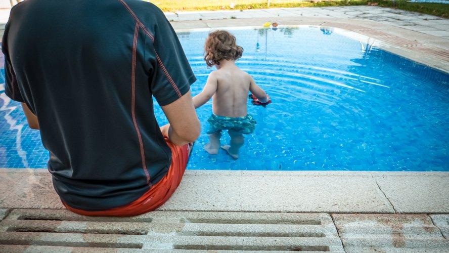 adulte qui surveille un enfant dans la piscine