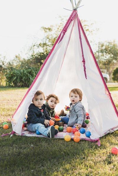 trois enfants jouent dans un tipi